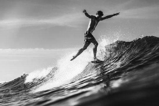 Silhouette of man in the ocean surfing wave in bright day light. Stylish pose. Black and white image.