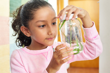 Young girl with a grasshopper in a jar