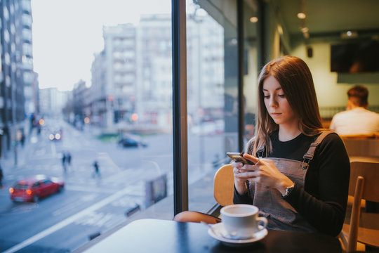 younger woman taking coffee at dusk