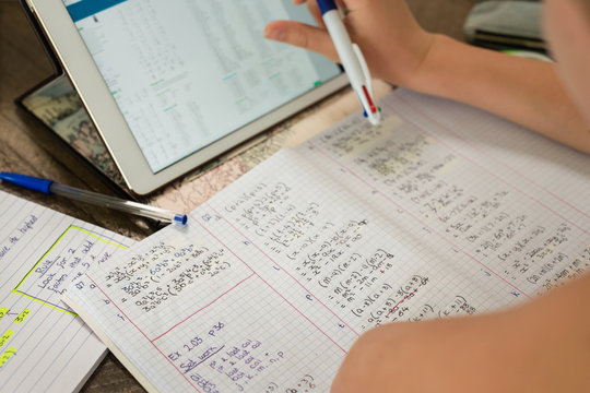 high school student doing maths homework at home