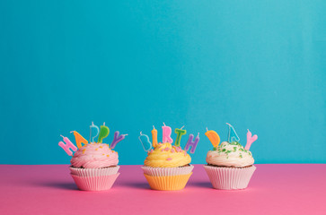 Cupcake with birthday candle on a blue background