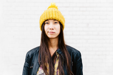 Woman in a yellow knitted hat standing against a gray wall
