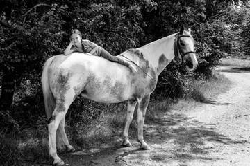 Das junge Mädchen liegt auf dem weißen Pferderücken und lächelt, schwarz/weiß