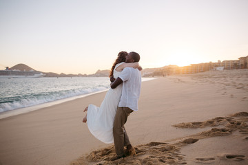 Affectionate, happy just-married couple together at sunset on th