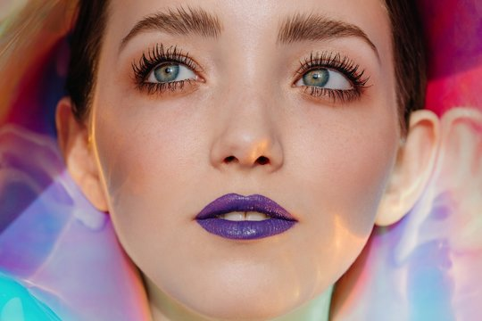 Closeup portrait of young woman with unusual beauty and violet lips by the holographic background