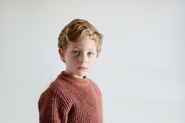 Portrait of a beautiful six year old child looking at camera with and plain white background