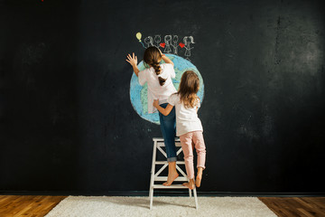 Two girls drawing planet earth on a blackboard