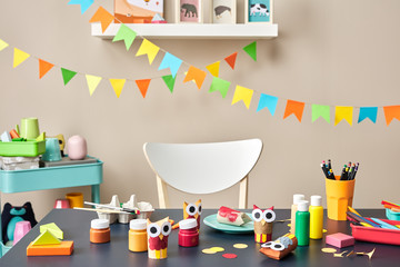 Desk of prechool child with colorful garlands with flags in back