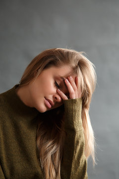 Tired blonde woman touching head