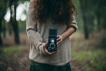 woman with retro camera making pictures in the woods
