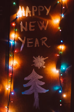 Happy new year lettering on wooden board