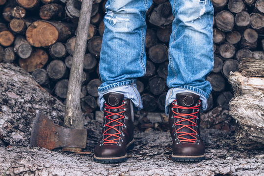 male legs in jeans and mountaineering boots on wooden background with an axe