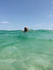 Young female model jumps and swims in tropical ocean beach
