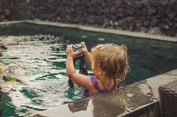 Little girl using underwater video camera in pool
