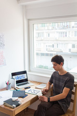 Modern urban teenage boy at using mobile phone next to working table