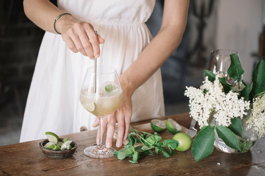 Crop woman mixing cocktail