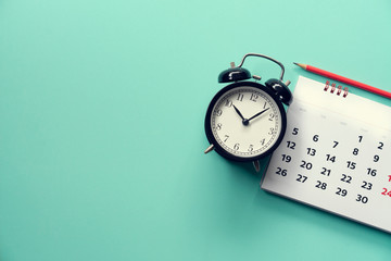 close up of calendar and alarm clock on the green background, planning for business meeting or...