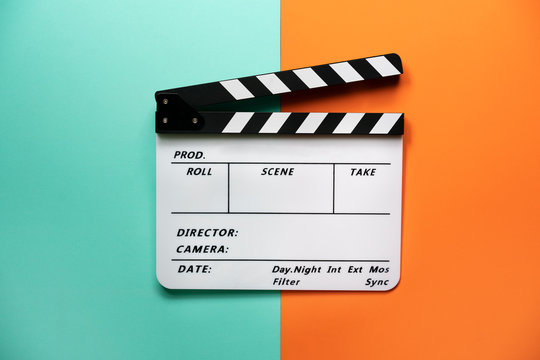 movie clapper on color table background; film, cinema and video photography concept