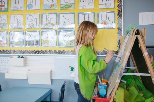 Young girl painting in classroom