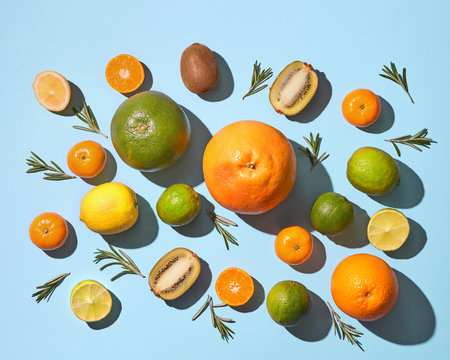 Mix of colored fruits with rosemary on blue background