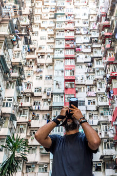Photographer taking pictures of residencial buildings facades in Hong Kong