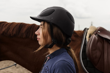 Young woman in outfit of horse rider
