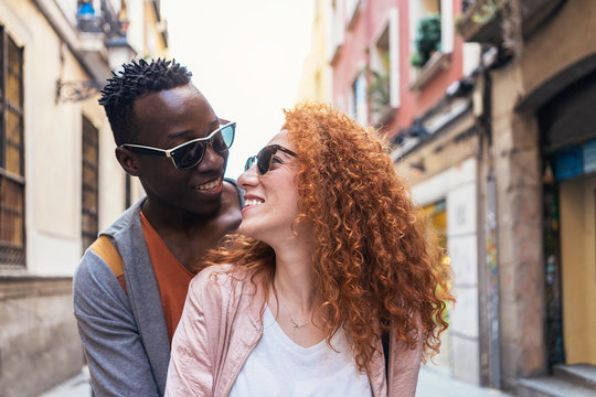 Multiethnic young couple having romantic moments together in the street
