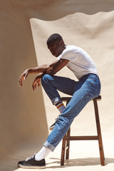 Young man poses in white tshirt and jeans