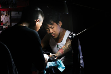 Professional asian tattooer makes a tattoo