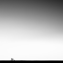 Silhouette of couple walking a dog