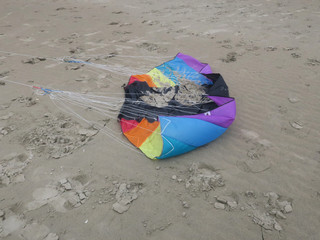 crinkled kite in rainbowcolors with white threads laying on the beach of Velsen Netherlands