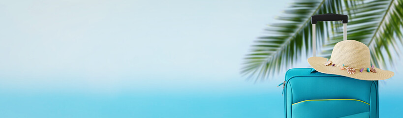 Wall Mural - holidays. travel concept. blue suitcase with female hat infront of tropical background. banner