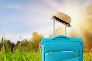 Wall Mural - recreation image of traveler luggage and fedora hat in.front of a rural landscape. holiday and vacation concept