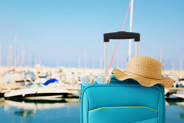Wall Mural - holidays. travel concept. blue suitcase with female hat, sunglasses in front of tropical marina background