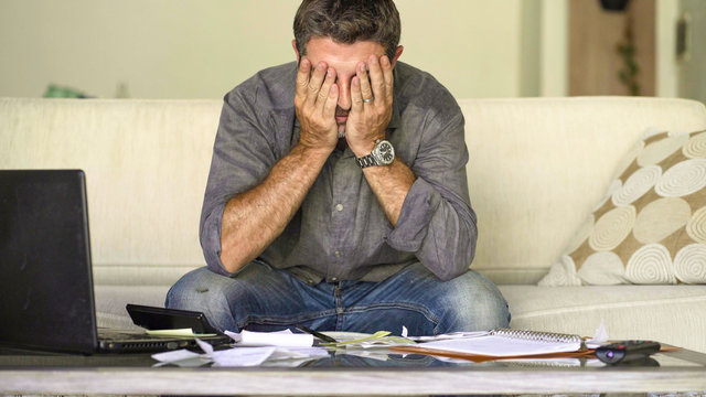 stressed and desperate man at home living room couch doing domestic accounting with paperwork and calculator feeling overwhelmed and worried suffering financial crisis