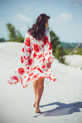 Fashion outdoor photo of beautiful sensual woman with long dark hair in swimwear on the sand beach.