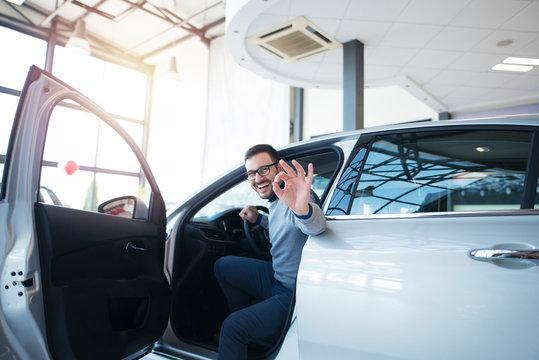 Car dealer or car buyer sitting in brand new vehicle showing okay hand gesture. Satisfied customer at vehicle dealership showroom.