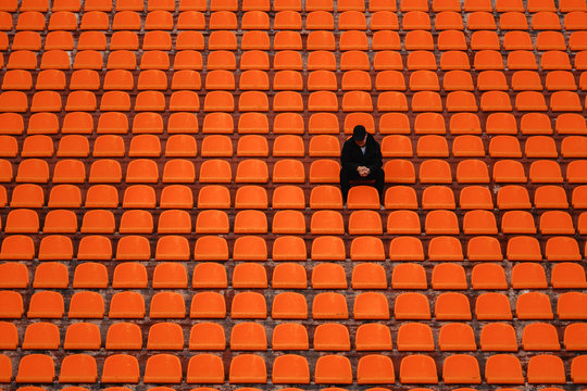 lonely man on the empty stadium seat cheering for the team, one man army concept