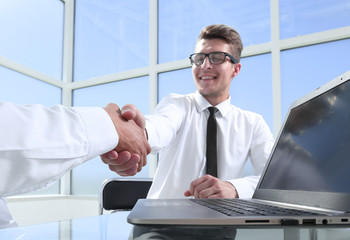 Satisfied entrepreneurs shaking hands after negotiations on meeting in office