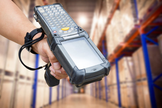 close up hand of worker holding barcode scanner with warehouse background.