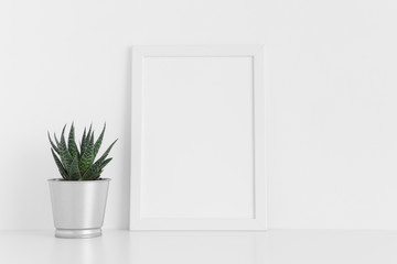 White frame mockup with a cactus in a pot on a white table. Portrait orientation.