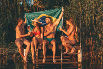 Happy group of young people drinking beer with a Brazilian flag on a dock by the river during the summer sunny day
