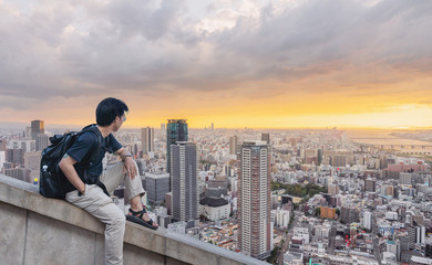 Wall Mural - a man with backpack looking at city view in sunset in summer
