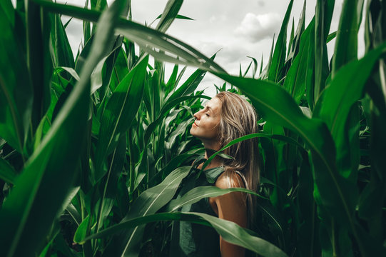 Young woman poses at corn field. Carefree woman enjoying freedom outdoors.