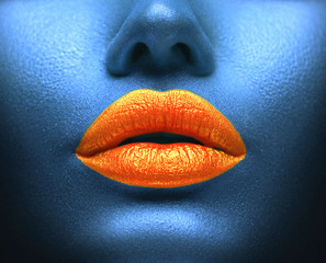 Creative colorful makeup. Bodyart, lipgloss on sexy lips, girl's mouth. Orange lips on blue skin