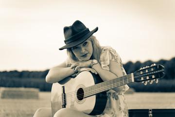 Countrysängerin mit Gitarre sitzt verträumt auf einem Strohballen, duotone