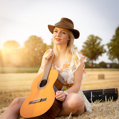 Hübsche, junge Sängerin mit Gitarre auf einem Strohballen in der Abendsonne
