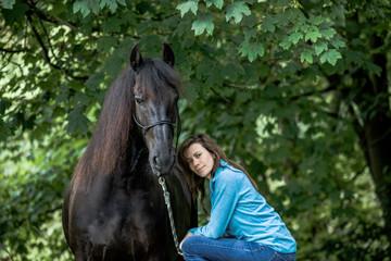 Eine Frau und ihr Pferd in der Natur, Friesenpferd