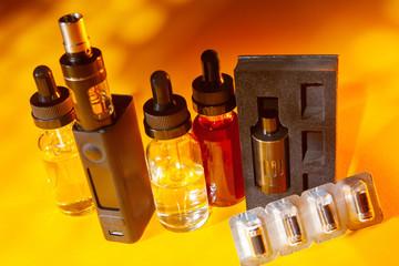 The vaping kit. Modern electronic cigarettes. Vaping devices. Smoking gadgets. E-cigs. Smoking mod. Bottles of liquids for vaping. Vapeshop. Alternative to smoking.