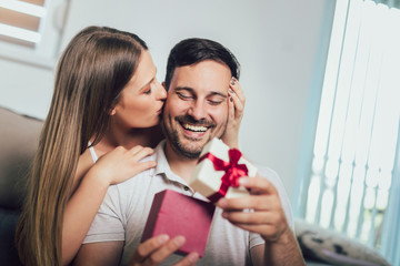 Woman surprising his boyfriend with a gift on the couch at home in the living room